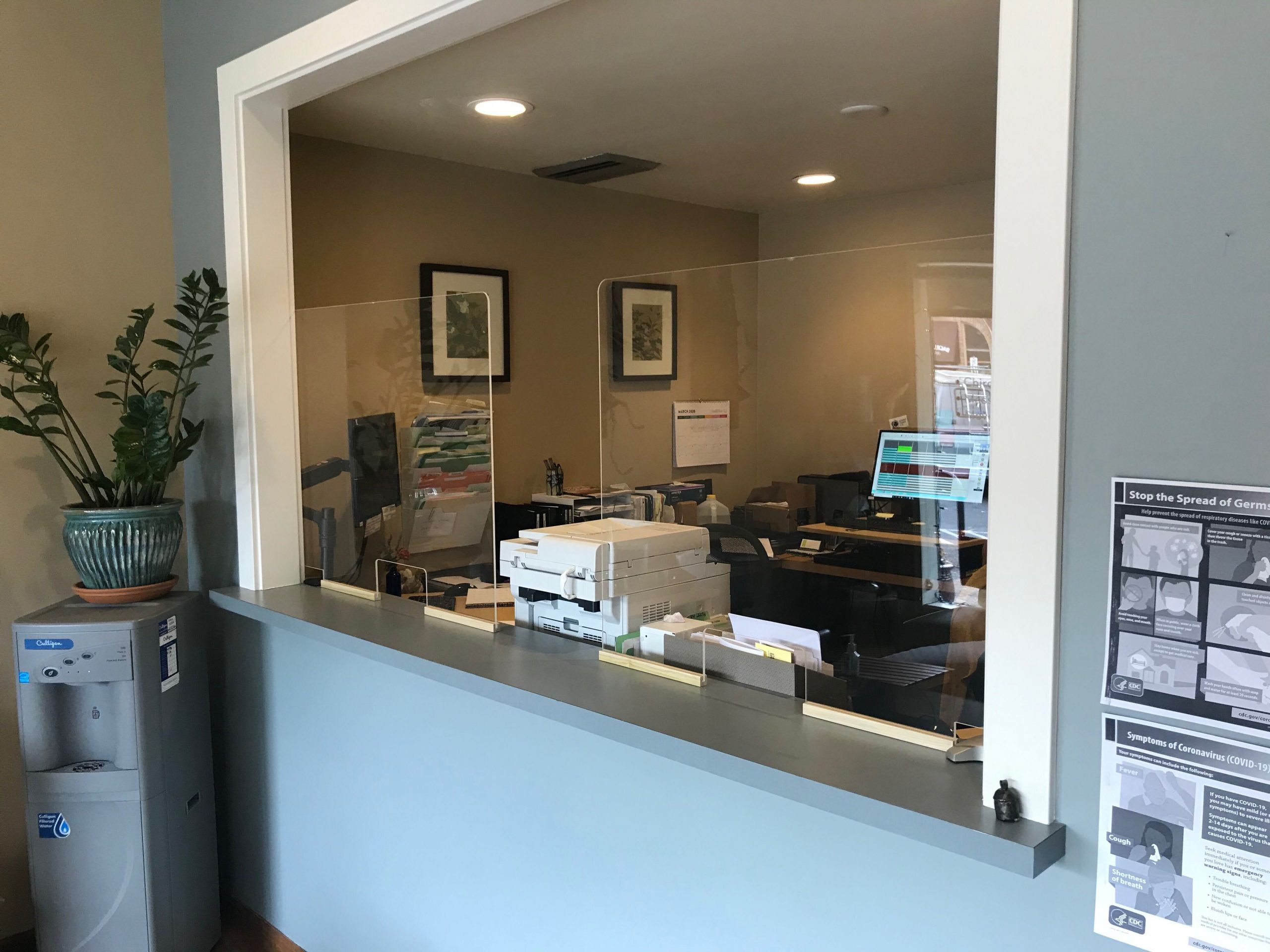 protective barrier sneeze guard installed at a front desk